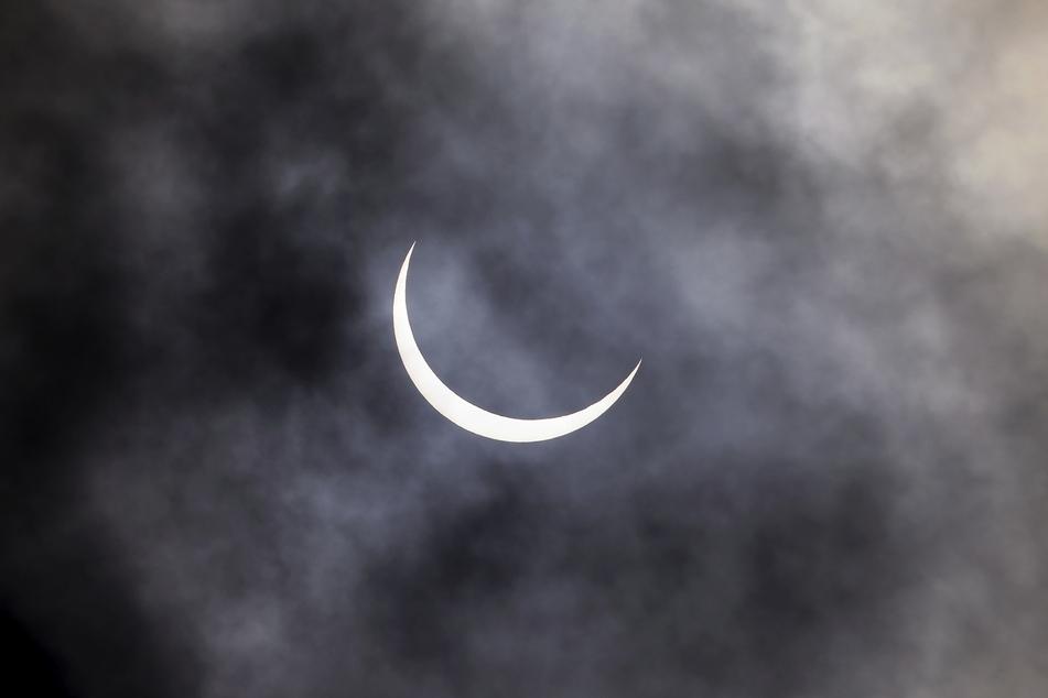 Indien, Neu Delhi: Die Sonnenfinsternis ist in Neu Delhi durch Wolken hindurch zu beobachten.