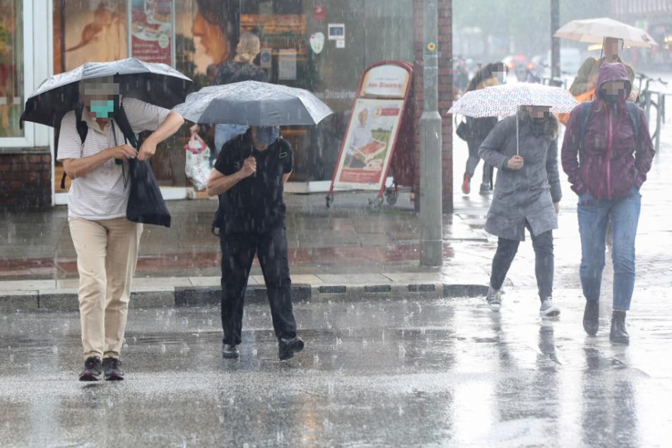 Passanten sind bei Starkregen in Hamburg unterwegs. (Symbolfoto)