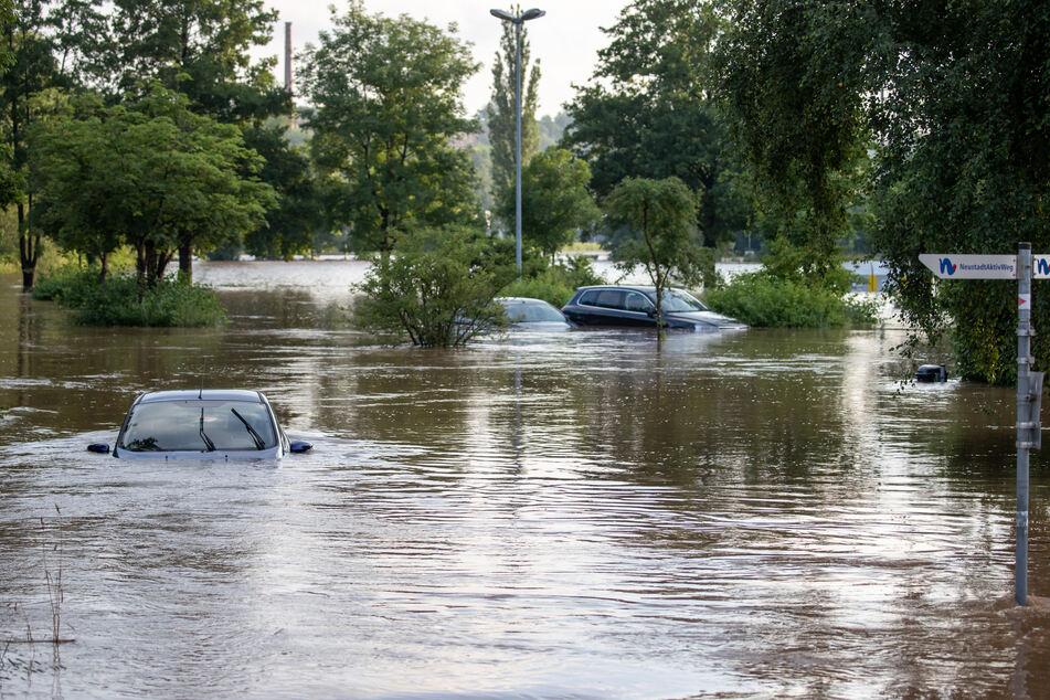 Autos stehen im Hochwasser, nachdem die Aisch im bayrischen Neustadt am Freitag über die Ufer getreten ist.
