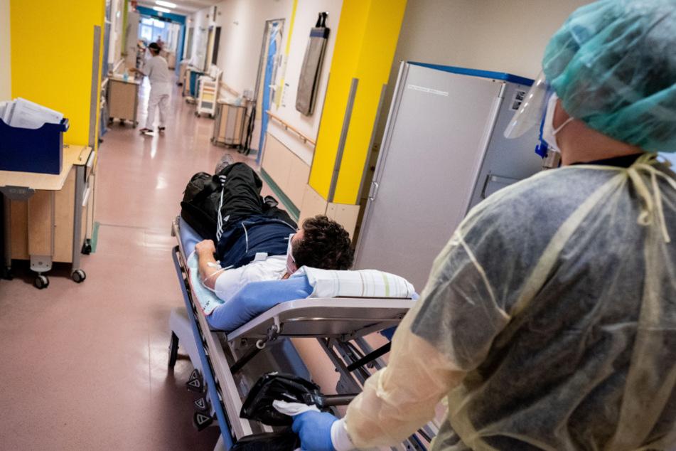 Der Stationsleiter schiebt einen Patienten zur Covid-19-Station des Krankenhauses Bethel Berlin.