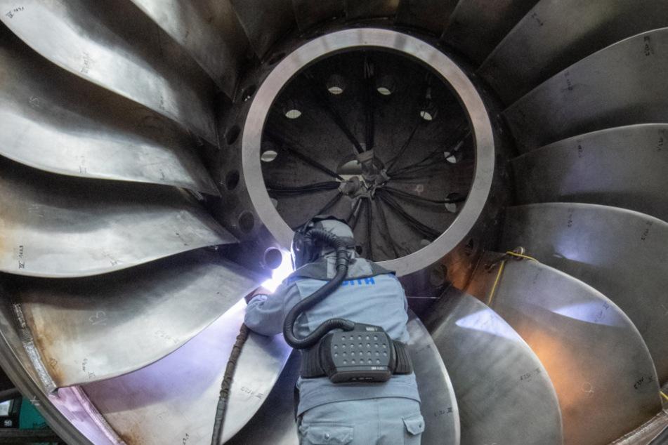 Ein Arbeiter eines Maschinen- und Anlagenbauers arbeitet an einer Wasserturbine.