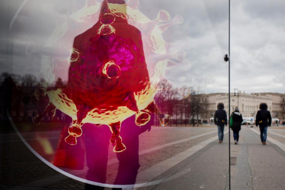 Passanten gehen neben einer Bushaltestelle mit einer elektronischen Werbetafel, auf der eine Illustration des Coronavirus zu sehen ist.