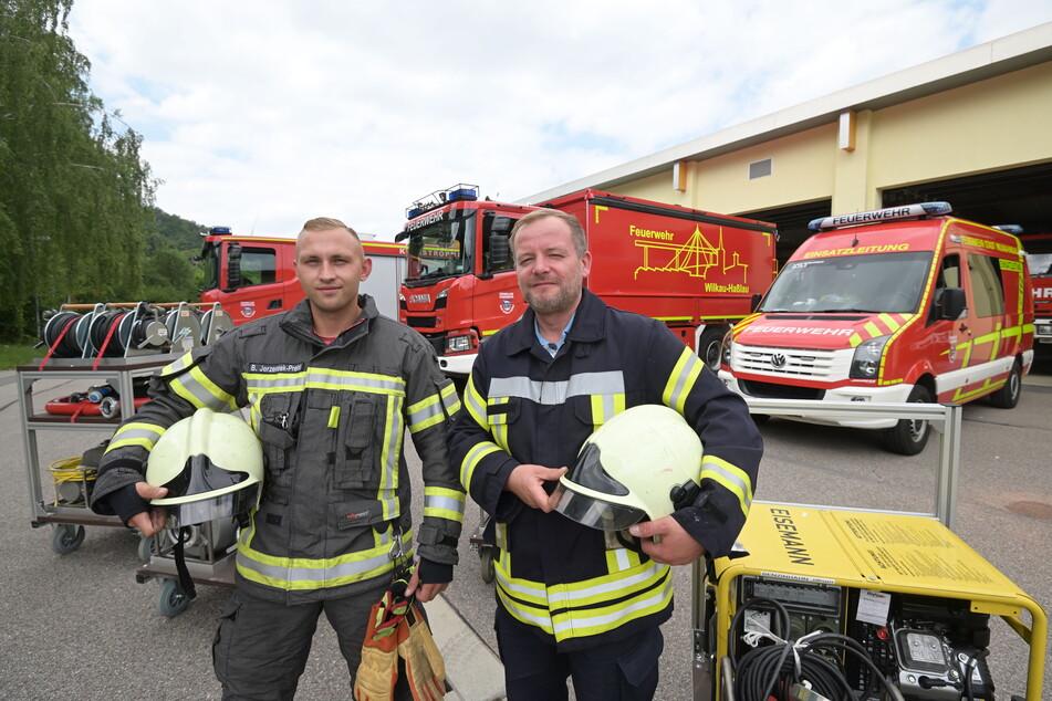 Björn Jerzembek-Preinl (29, l.) und Christian Schwieder (40) von der Freiwilligen Feuerwehr Wilkau-Haßlau stehen vor den einsatzbereiten Fahrzeugen.