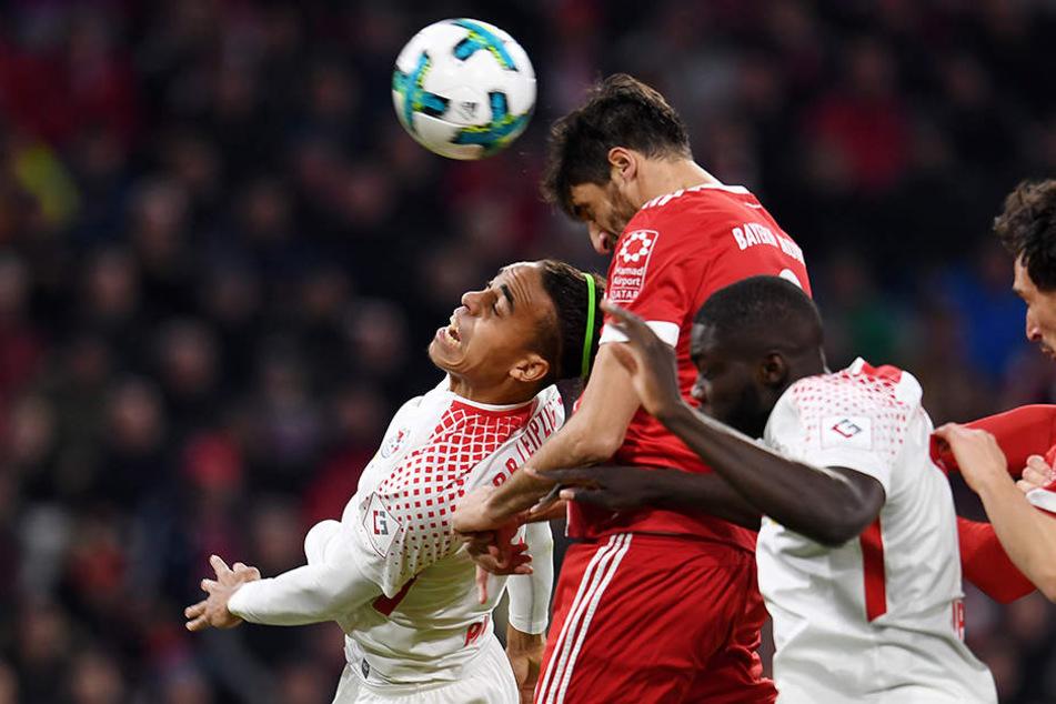 Yussuf Poulsen (l.) von Leipzig, Javier Martinez (m.) von Bayern und Dayot Upamecano (r.) von RB Leipzig kämpfen um den Ball.