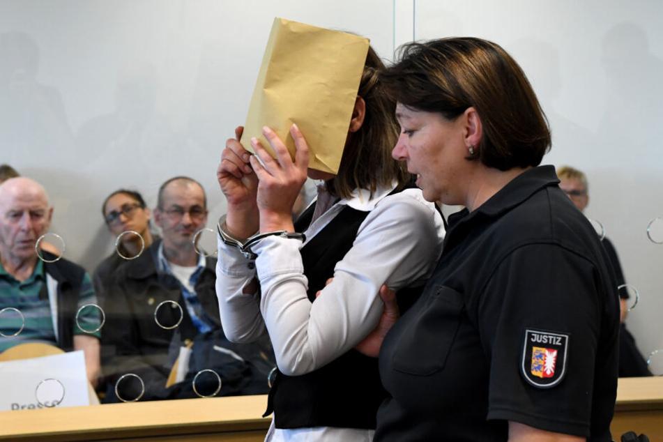 Mit verdecktem Gesicht wird die Angeklagte in den Gerichtssaal geführt.