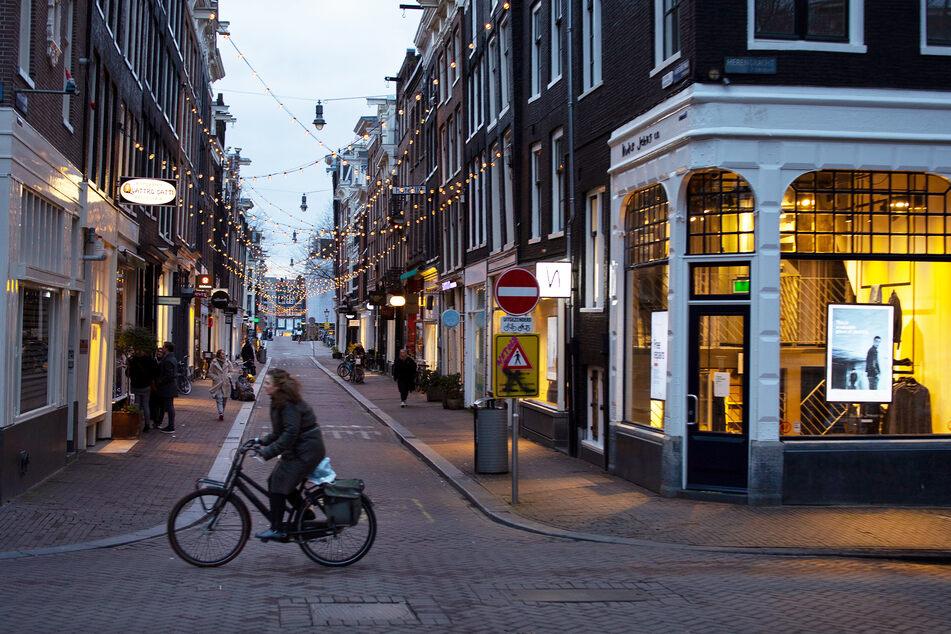 Eine Frau fährt auf ihrem Fahrrad durch das ansonsten fast leere Einkaufsviertel der Neun Straßen in Amsterdam.