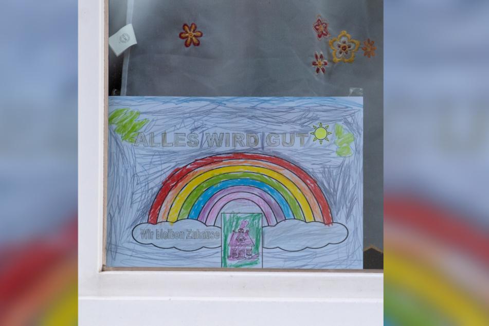 """Ein Blatt Papier mit einem Regenbogen und der Aufschrift """"Alles wird Gut - Wir bleiben Zuhause"""" hängt in einem Fenster zur Strassenseite in München."""