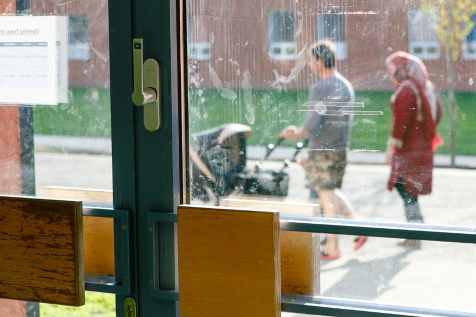 Eine Familie geht im Außenbereich der Flüchtlingsunterkunft in Boostedt spazieren.
