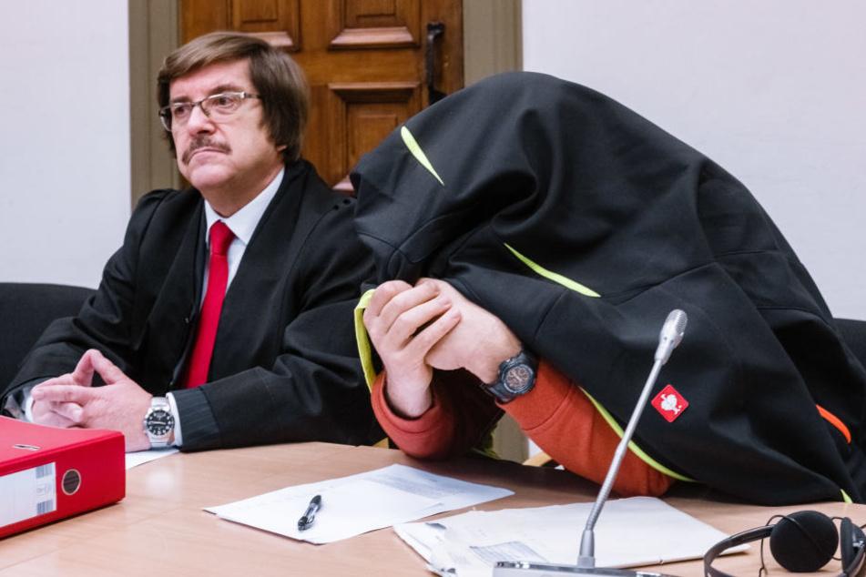 Der Angeklagte sitzt zum Prozessauftakt mit einem Kleidungsstück über dem Kopf neben seinem Anwalt Wolfgang Wenskat.