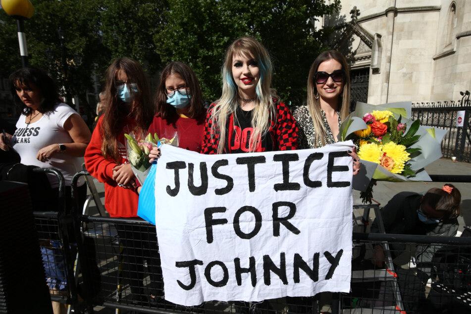 """Fans von US-Schauspieler Johnny Depp (57) halten am letzten Tag der Anhörungen im Verleumdungsprozess von Depp gegen den Verlag der Boulevardzeitung """"The Sun"""" vor dem High Court in London ein Banner mit der Aufschrift """"Gerechtigkeit für Johnny"""" hoch."""