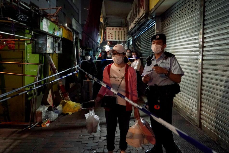 Eine Bewohnerin mit Mund-Nasen-Schutz wartet im gesperrten Bereich des Bezirks Sham Shui Po darauf, nach Hause zu gehen.