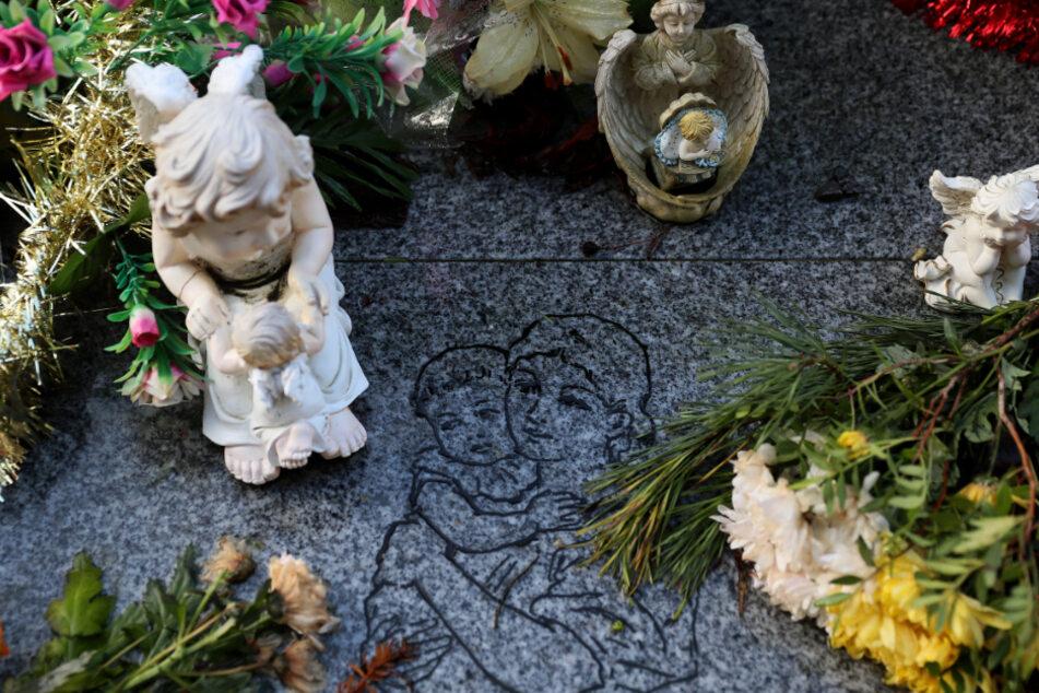 Blumen und Engel-Figuren liegen an einer Gedenkstätte für 222 Kinder aus dem Bethany Mother and Child Home auf dem Friedhof Mount Jerome.