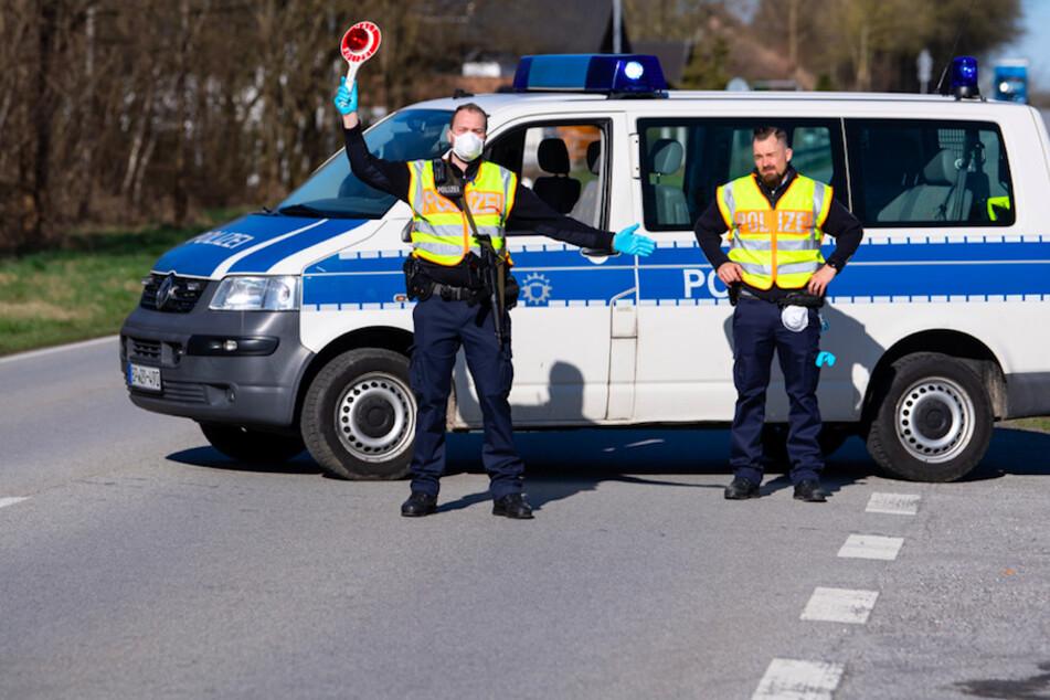 Polizisten stehen an der Bundesstraße 512 in der Nähe von Neuhaus am Inn an einer Kontrollstelle an der Grenze zu Österreich.
