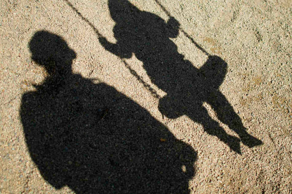 Der Schatten von einem Mann und einem schaukelnden Kind fallen auf Sand auf einem Spielplatz.