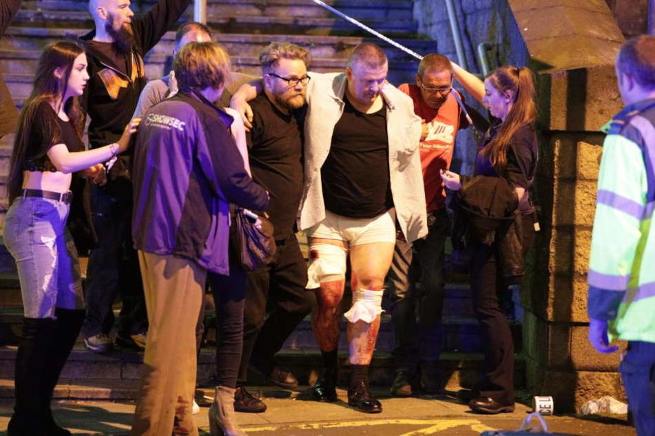 Einer verletzten Person wird in der Nähe der ManchesterArena geholfen.