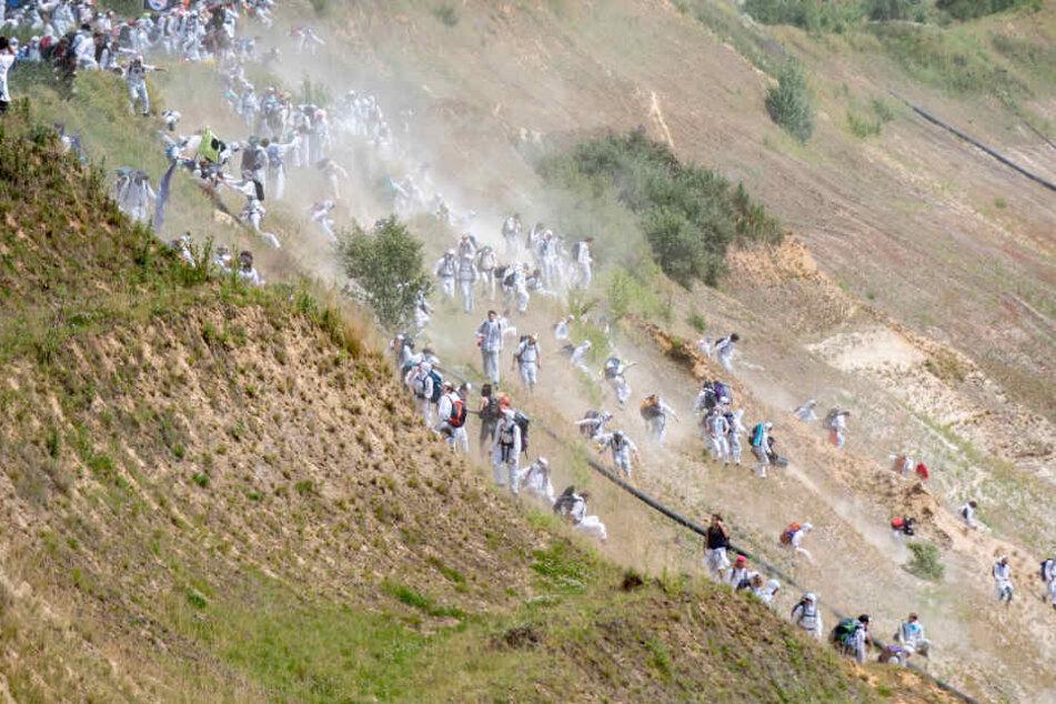 Zahlreiche Umweltaktivisten laufen in den Tagebau Garzweiler, nachdem sie die Polizeisperre durchbrochen haben.