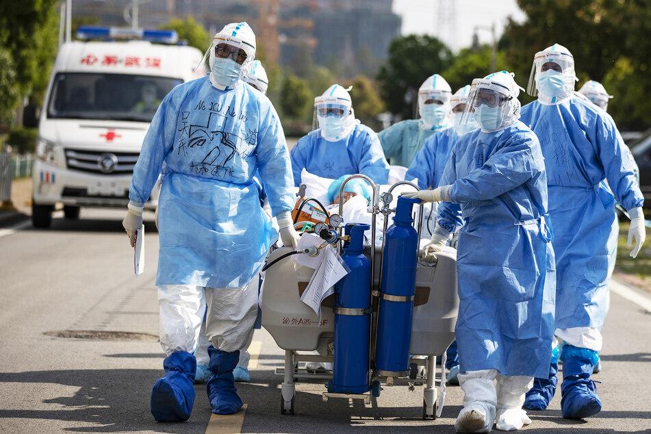 Medizinisches Personal in Schutzanzügen schieben einen Covid-19-Patienten in einem Bett über eine Straße, um ihn in die Intensivstation zu verlegen.