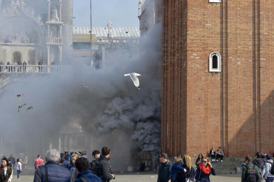 Rauch quillt am 17.03.2017 an der Fassade eines Gebäudes am Markus-Platz in Venedig  (Italien). Nach Medienberichten wollten Räuber mit Rauchbomben Panik  unter den Touristen verbreiten und dann einen Juwelier überfallen.