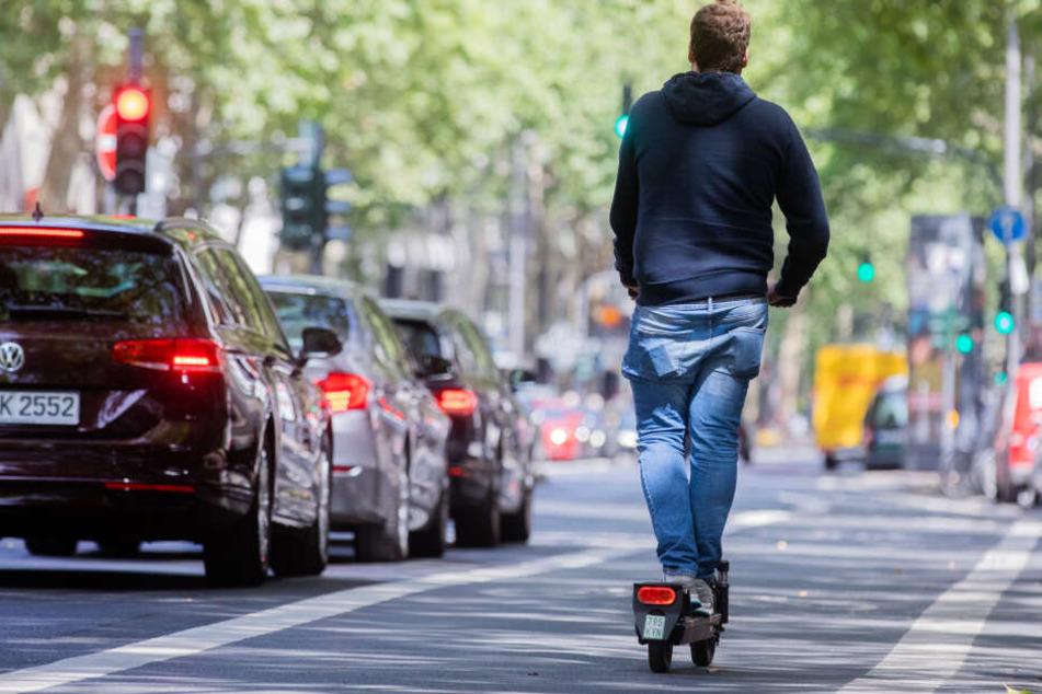 Ein E-Scooter-Fahrer unterwegs in Köln.
