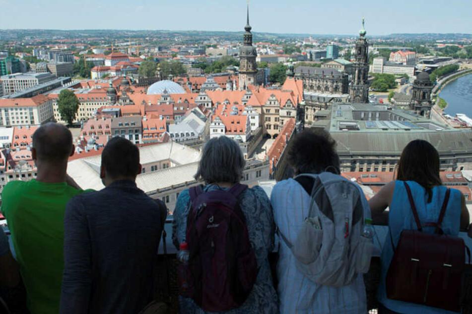 Touristen stehen auf der Kuppel der Dresdner Frauenkirche und blicken über die Altstadt.
