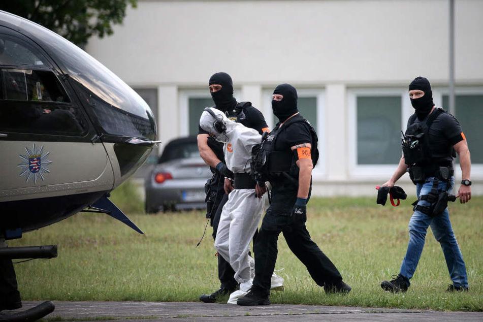 Ali B. wird von Polizisten in einen Hubschrauber geführt.