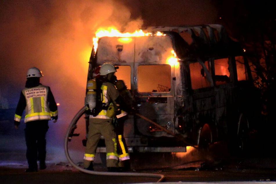 Feuerwehrleute versuchen das brennende Wohnmobil zu löschen.