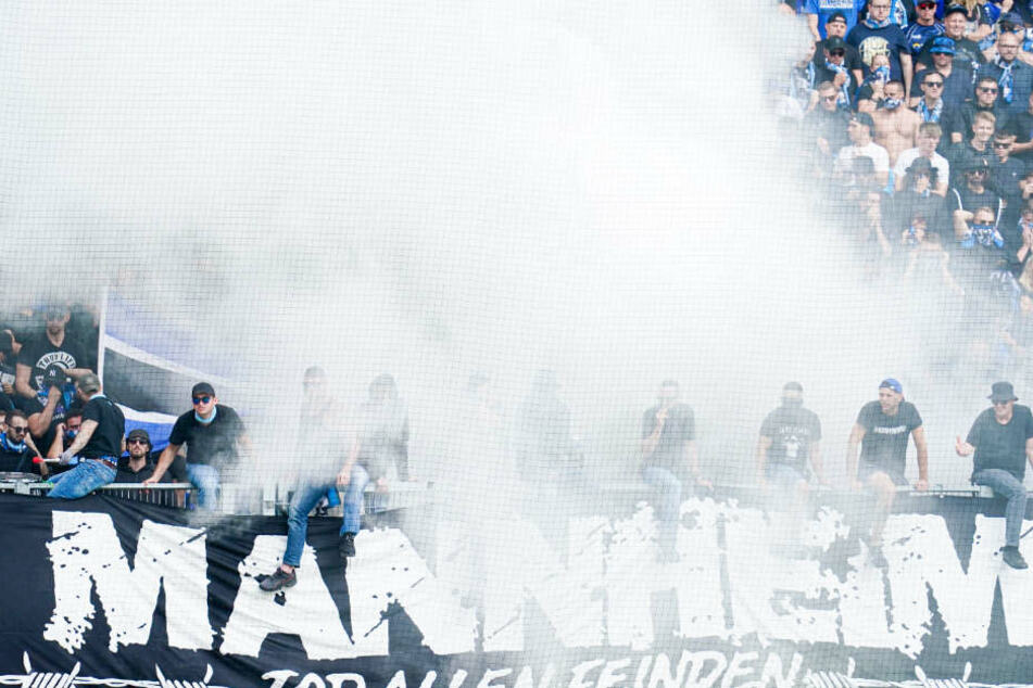 Hinspiel: Fans vom SV Waldhof stehen im Rauch auf der Gästetribüne des Fritz-Walter-Stadions in Kaiserslautern.