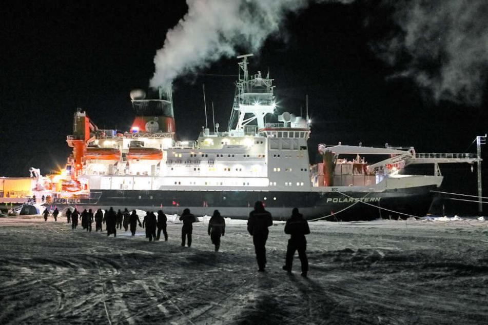 """Expeditionsteilnehmer gehen in Richtung des Forschungsschiffs """"Polarstern""""."""