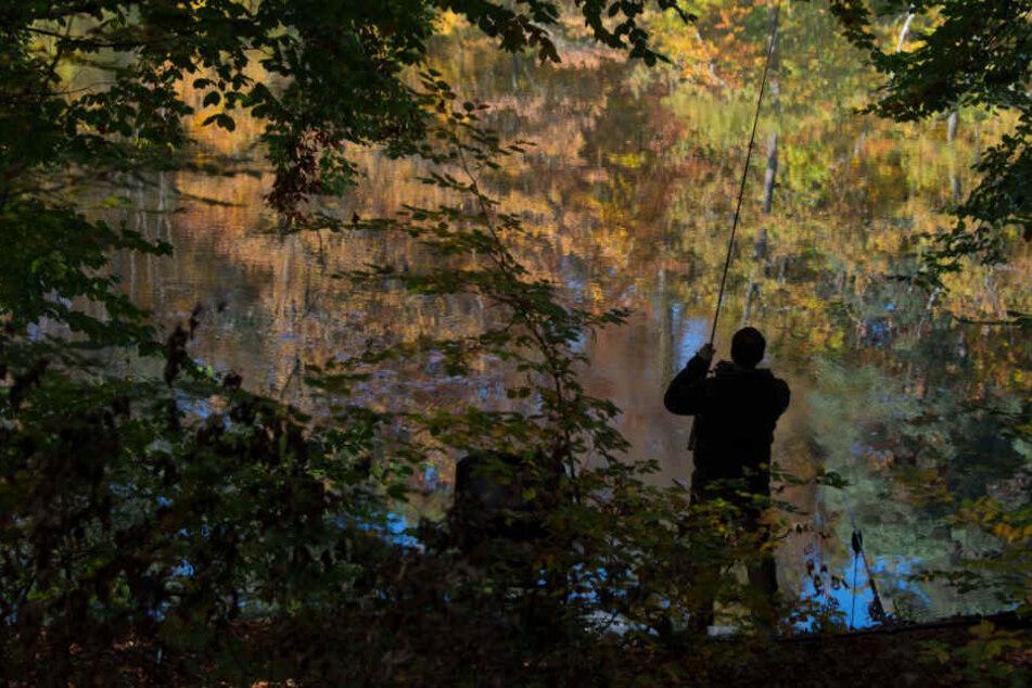 Ein Angler steht vor einem Gewässer. (Symbolbild)