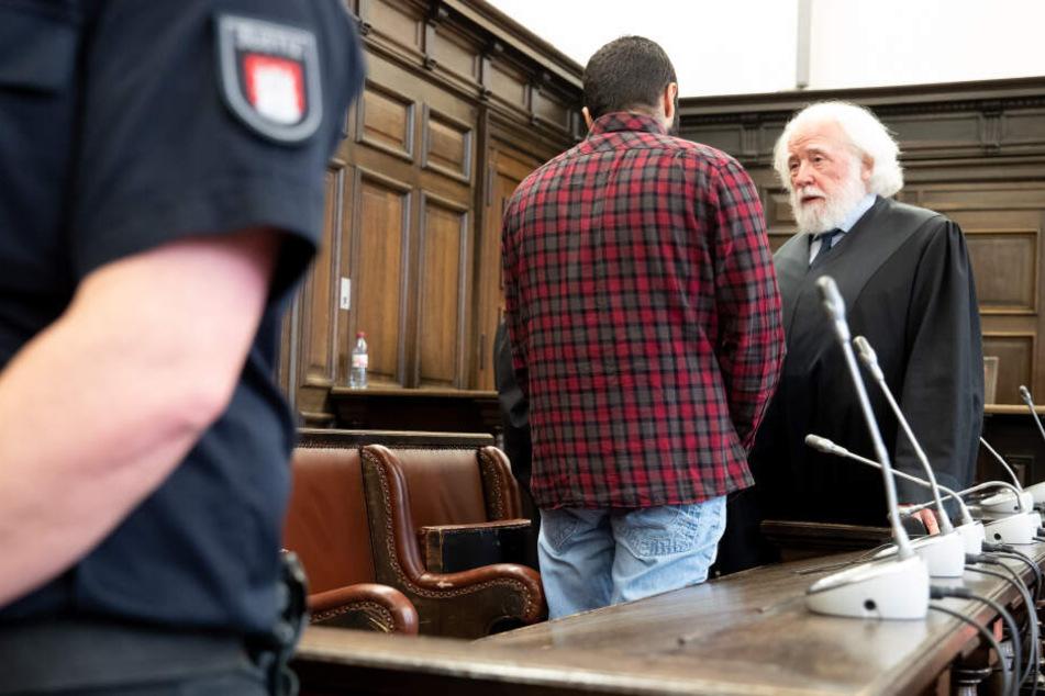 Der Angeklagte unterhält sich mit seinem Anwalt im Gerichtssaal.