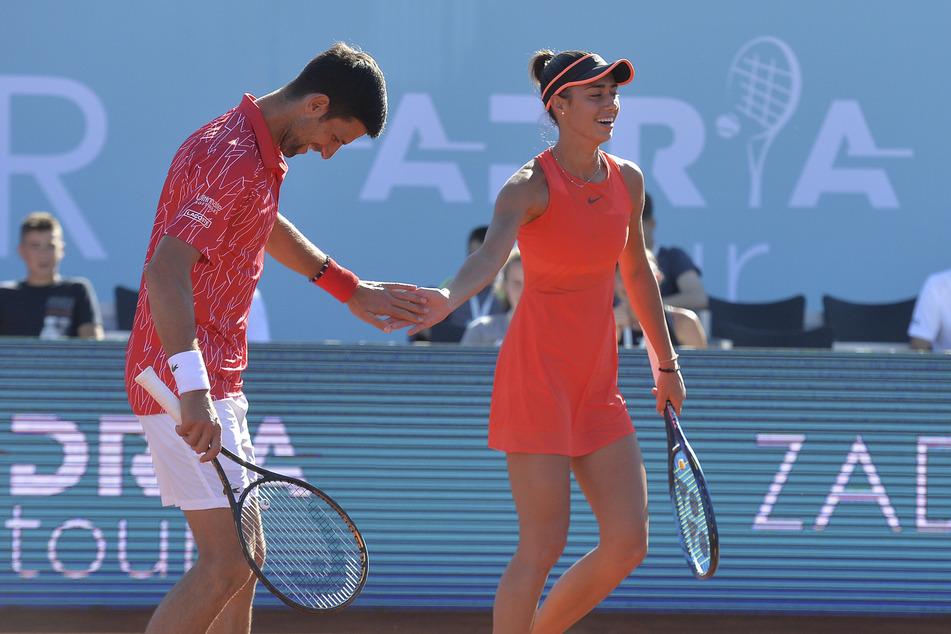 Novak Djokovic, Tennisspieler aus Serbien, gibt Olga Danilovic, Tennisspielerin aus Serbien, bei einem Doppelspiel der Adria-Tour die Hand.