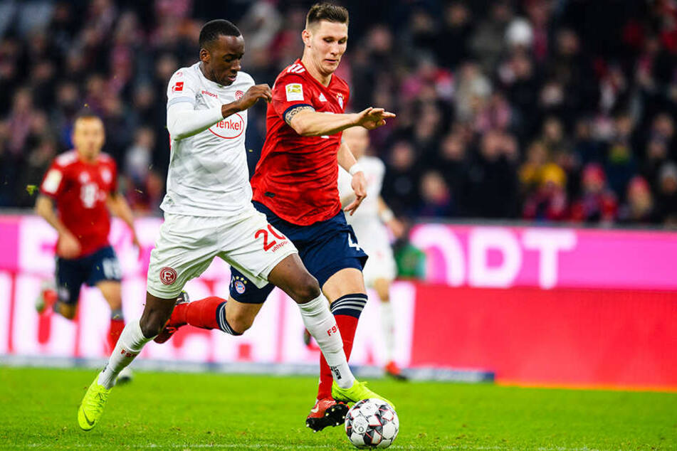 Düsseldorfs Dodi Lukebakio (l.) sprintet Bayerns Innenverteidiger Niklas Süle (r.) davon.