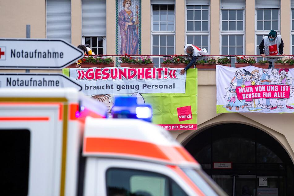 """Krankenhaus-Mitarbeiter befestigen am Klinikum Schwabing während eines Warnstreiks Plakate mit der Aufschrift """"Gesundheit braucht genug Personal"""" und """"Mehr von uns ist besser für Alle""""."""