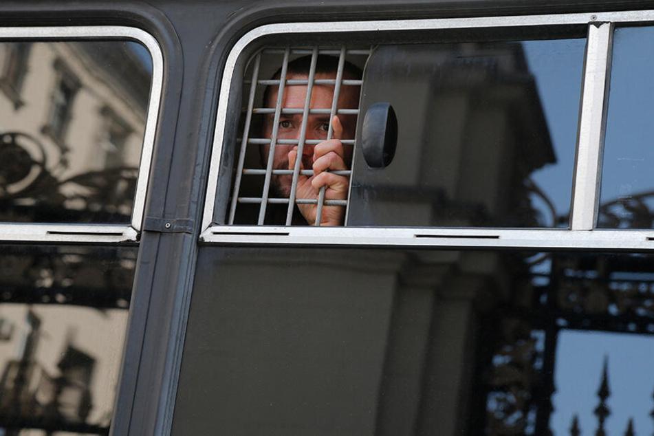 Ein Demonstrant wurde in einem Polizeibus festgesetzt.