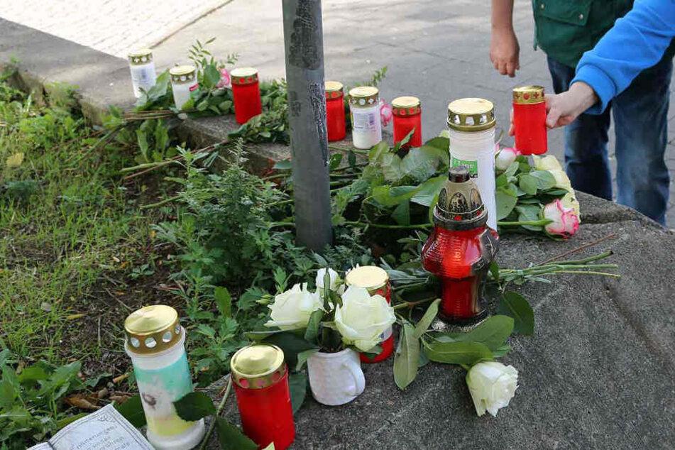 Menschen stellen Kerzen am Tatort in der Friedrichstraße auf.