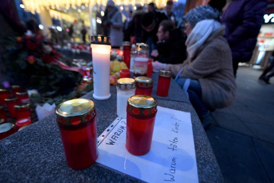 """Ein Grablicht steht auf einem Zettel """"Warum? Warum töten Kinder?"""" am Königsplatz."""