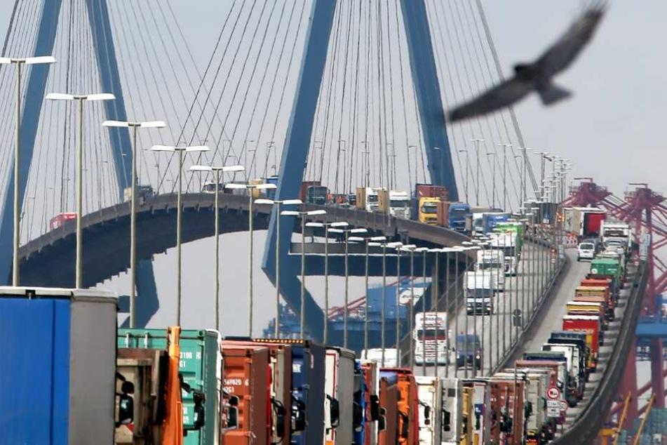 Mit Containern beladene Lastwagen stauen sich auf der Köhlbrandbrücke im Hafen.