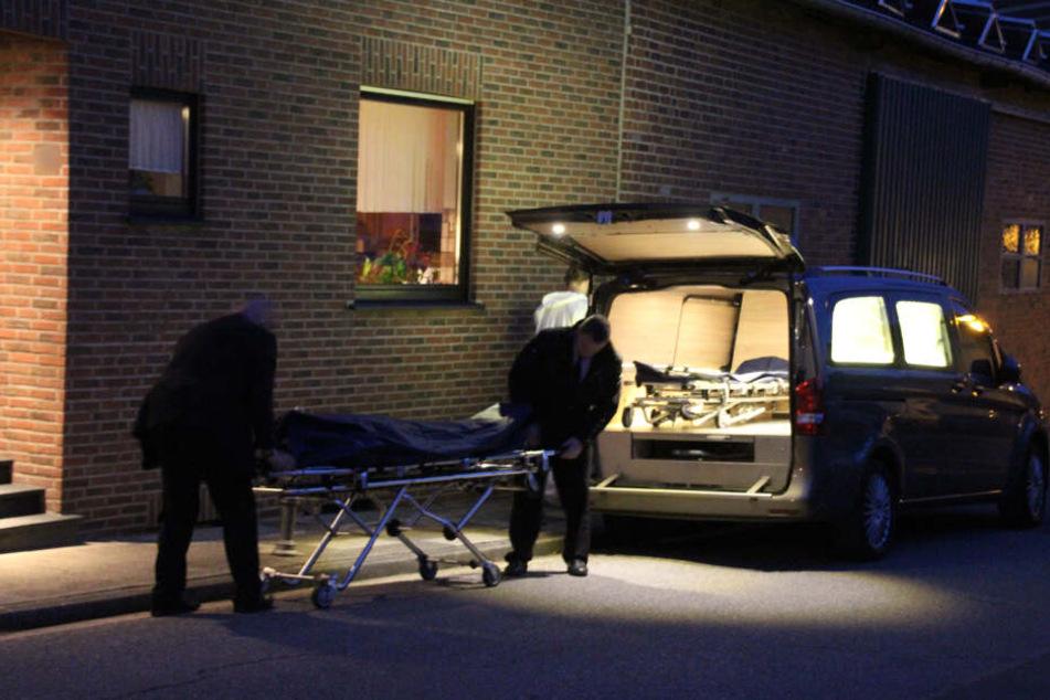 Bestatter tragen eine der zwei Leichen aus einem Wohnhaus in Hückelhoven/NRW.