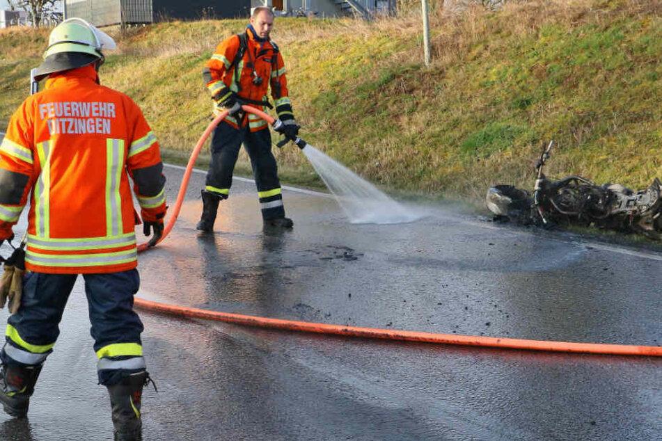 Feuerwehrmänner spritzen die Straße mit Wasser ab.