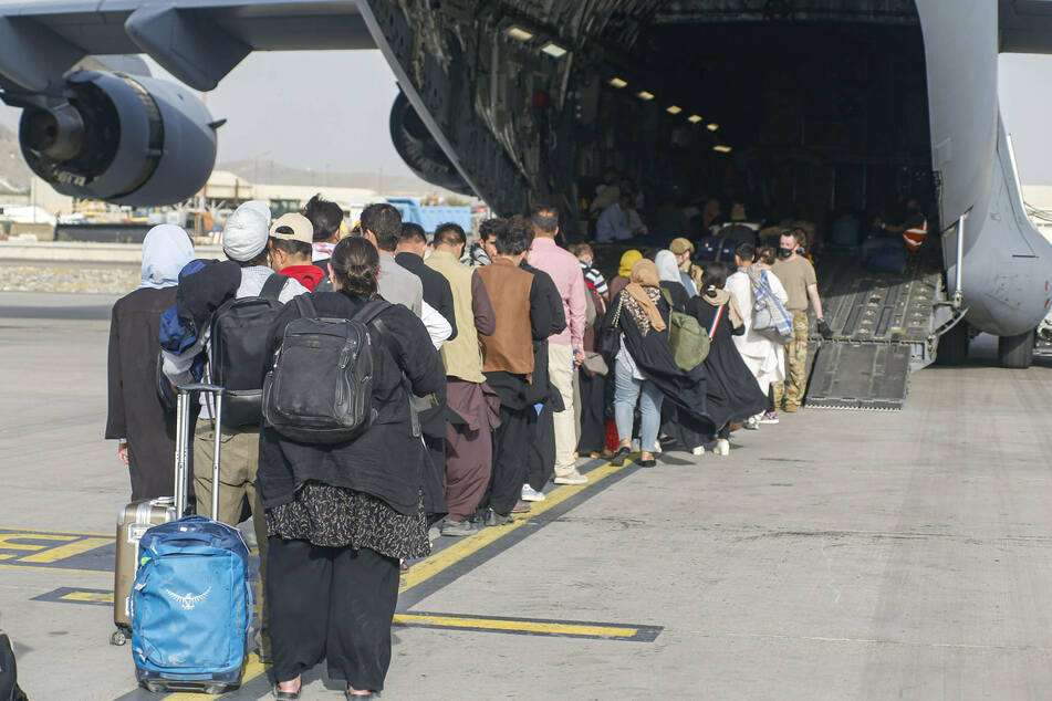 Evacuees board a plane departing from Kabul Airport in Afghanistan.