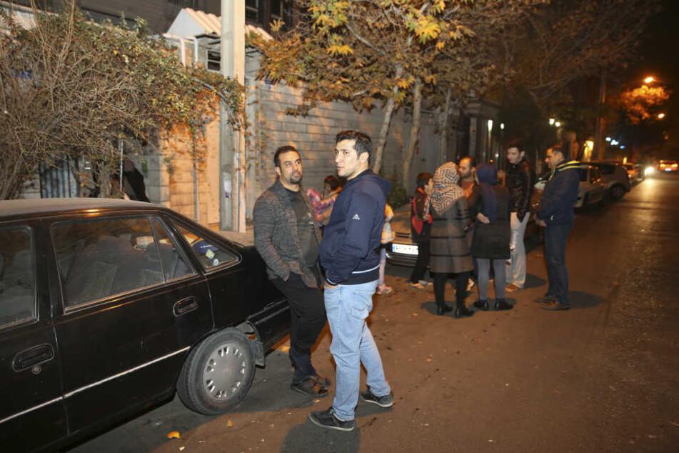 Menschen stehen in der Nacht auf der Straße. Viele wollen vorerst nicht in ihre Häuser zurück.