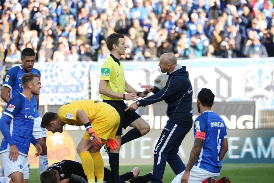 Kuriose Szene: Frank Steinmetz (2.v.r.) greift im Spiel zwischen Darmstadt gegen Magdeburg nach der Rudelbildung ein.