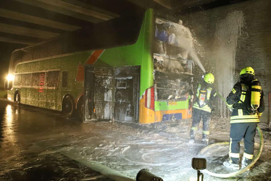 Feuerwehrmänner löschen den Brand am Flixbus.