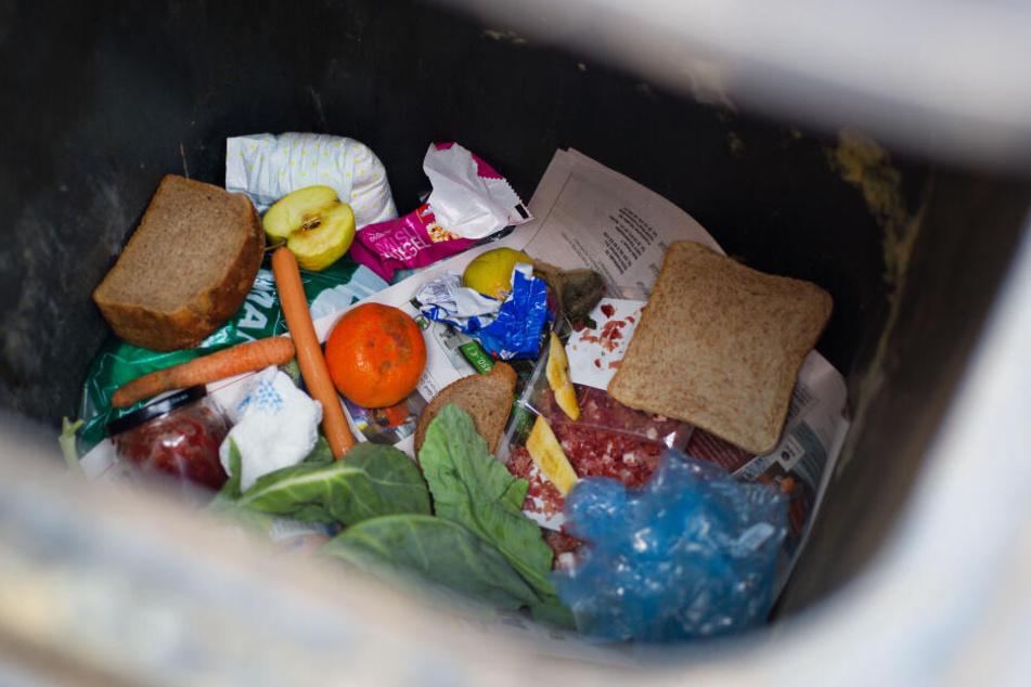 """Lebensmittel liegen in einer Mülltonne. Das """"Ansichnehmen"""" von entsorgten Lebensmitteln wird in Deutschland als Diebstahl geahndet."""