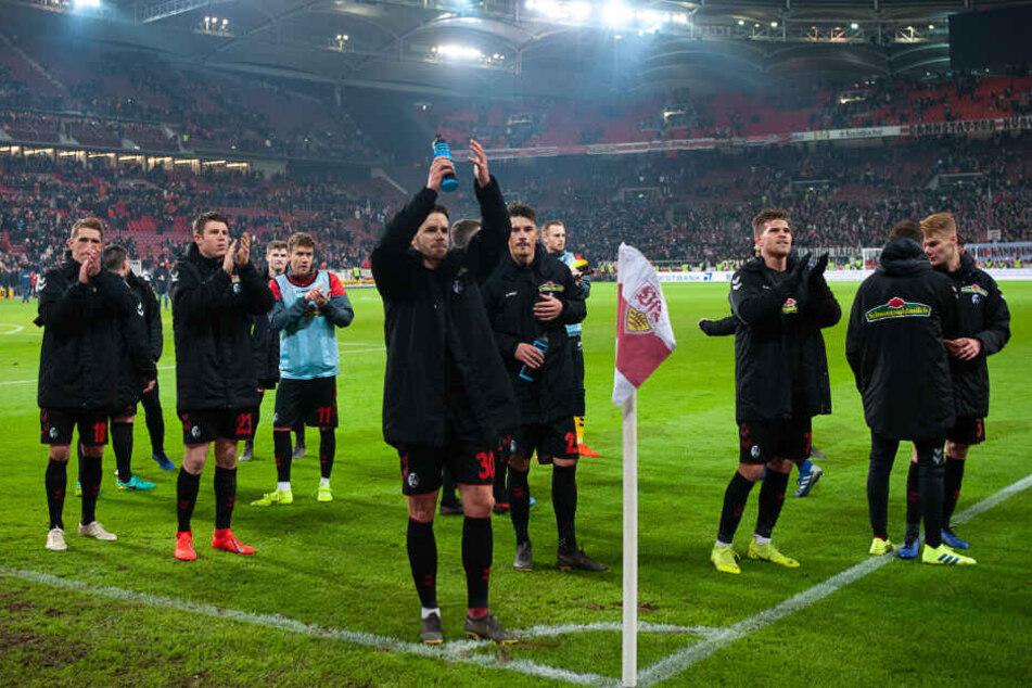 Freiburgs Spieler freuen sich nach dem 2:2 gegen den VfB Stuttgart im Stadion.