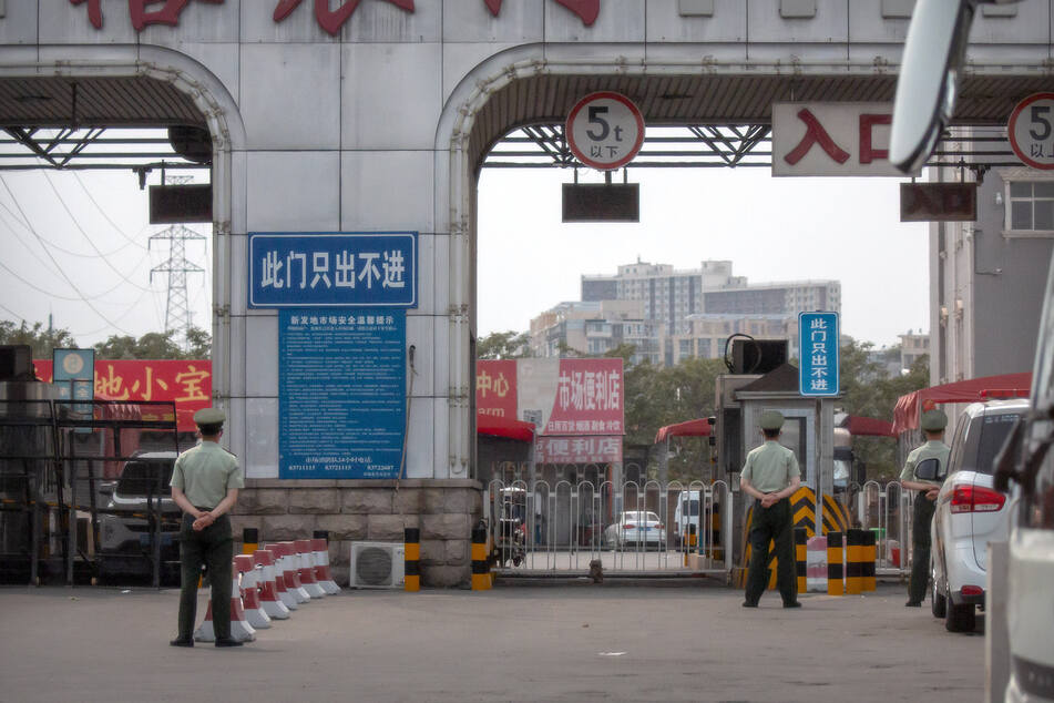 Polizisten halten vor den barrikadierten Eingängen des Xinfadi-Großmarktes Wache. Auf einem Großmarkt der chinesischen Hauptstadt wurden bei anfangs 500 Tests schon 45 Infektionen entdeckt.