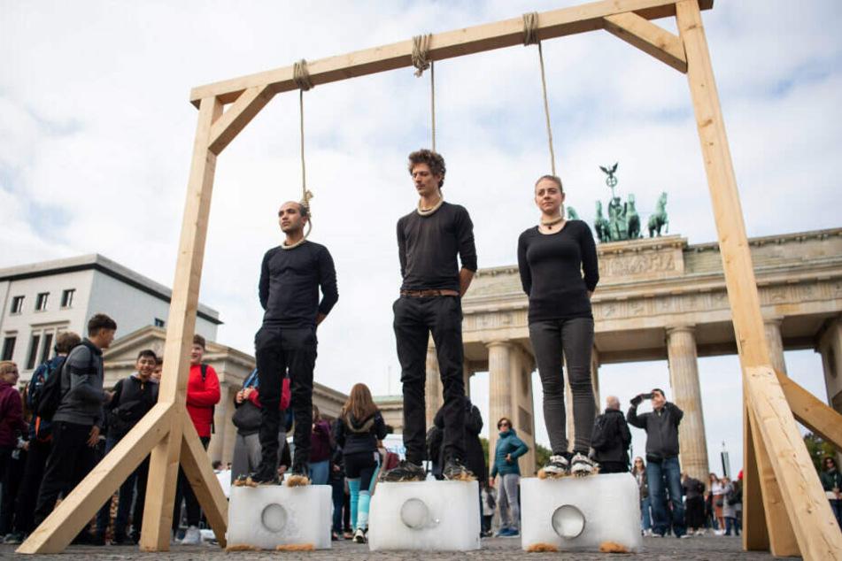 Drei Demonstranten stehen unter einem Galgen mit einem Seil um den Hals auf Eisblöcken.