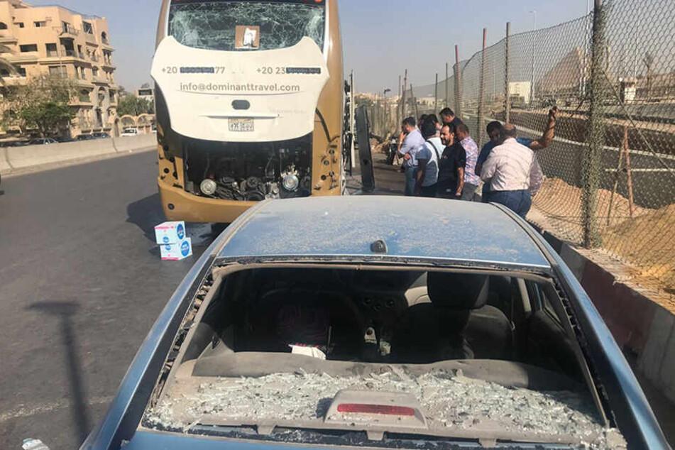 Menschen stehen neben einem Auto und einem Bus, die nach der Explosion teilweise zerstört wurden.
