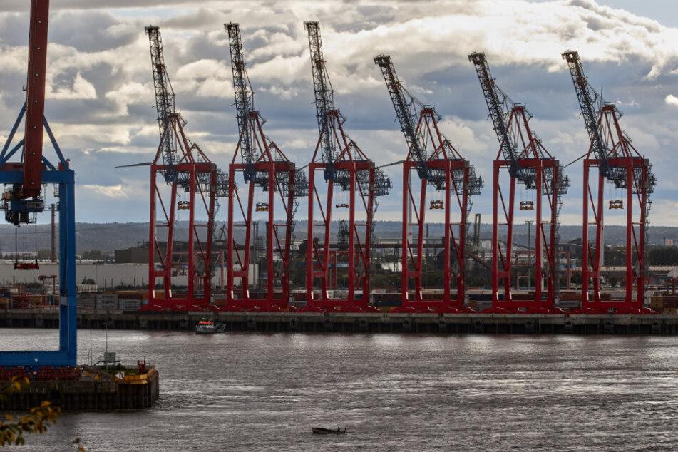 Die Kräne am Hafen hängen in einer Wolkendecke.