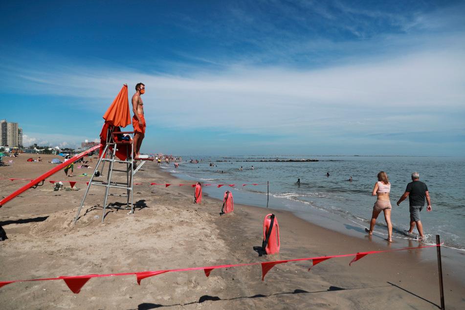 Ein Rettungsschwimmer mit Mundschutz steht am Strand von Coney Island an seinem Posten. Seit 1. Juni sind acht Strände in New York City offiziell zum Schwimmen geöffnet worden.